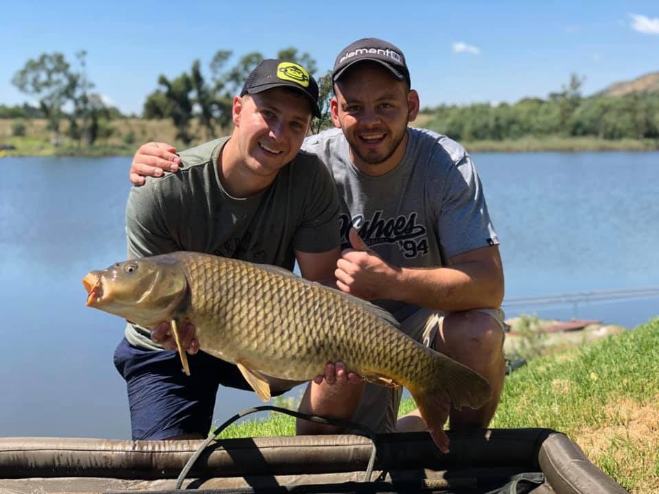 2 white millennials Friends posing with big common carp catch